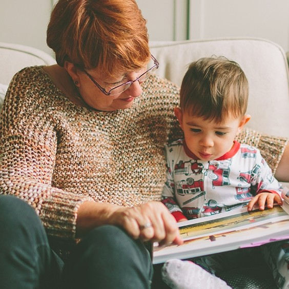 caucasian grandmother reading a book with her grandchild