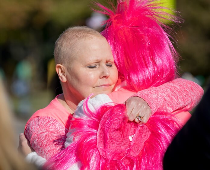 Two people hugging wearing pink at a Making Strides Against Breast Cancer event