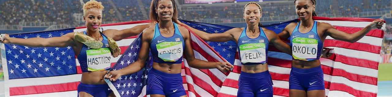 Four Olympic Track and Field stars with American flag posing for camera