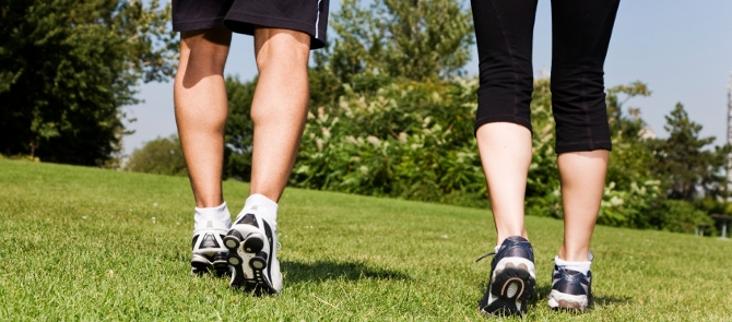 close up of man's and woman's legs as they walk through grass