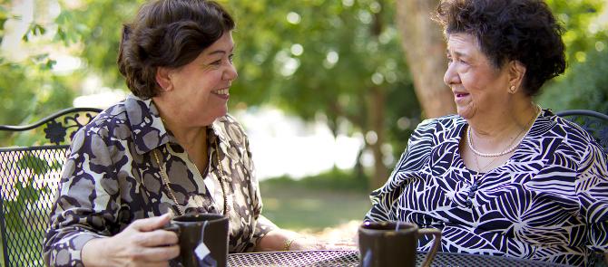 two women drinking tea outside