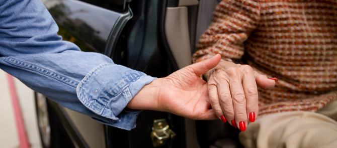 close up of caregiver helping woman out of car