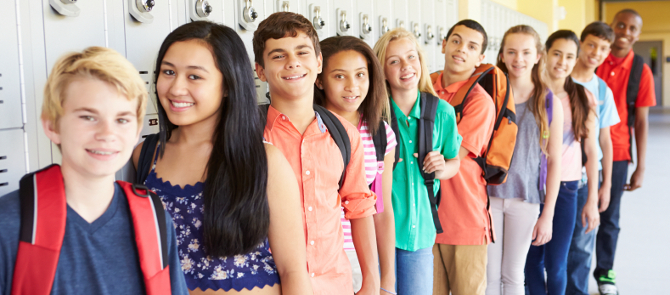group of smiling high school kids lined up in front of lockers