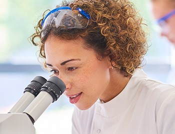 Female research scientist looking into a microscope in the lab