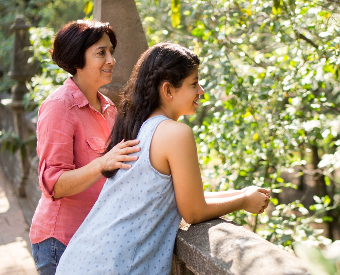 a mother and her teen daughter stand on a bridge overlooking greenery in a park
