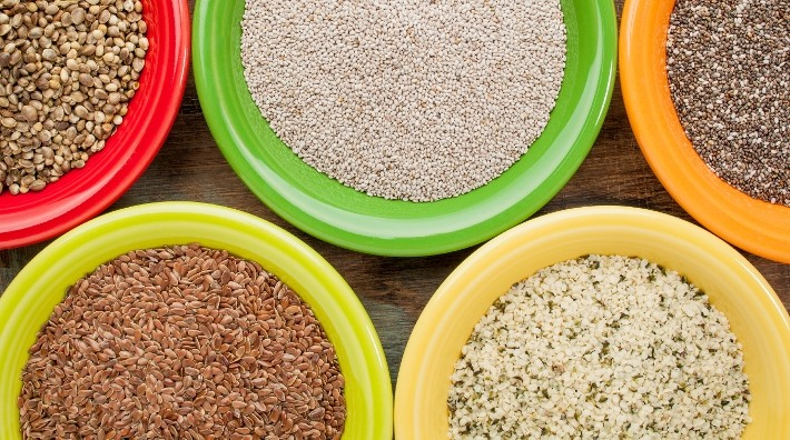 white and black chia, flax and hemp seeds in colorful ceramic bowls