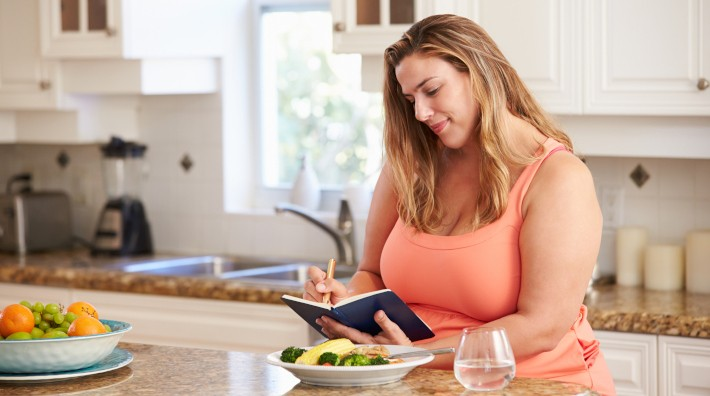 woman sitting at kitchen counter writing in her food diary