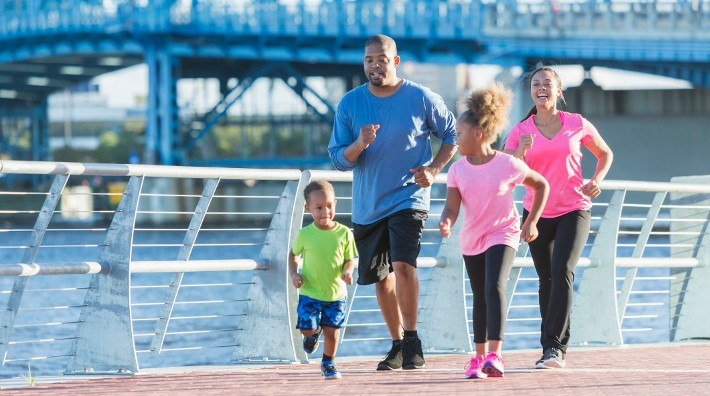 young family walks for exercise together along a river