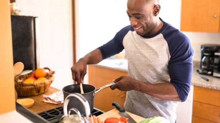smiling man cooking using assorted vegetables