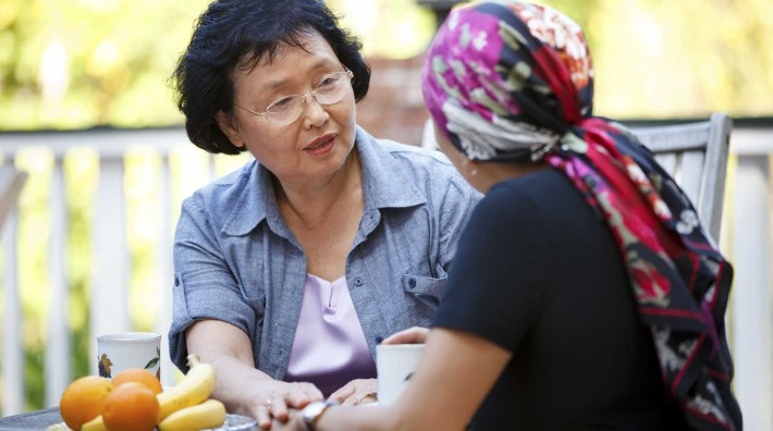 woman comforts and cancer patient in head scarf outside at table