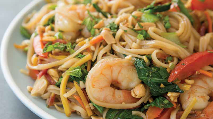 rice noodles with shrimp, bok choy and mint on a white plate
