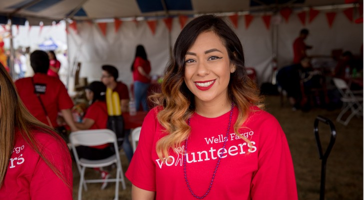 caucasian female at an event waring red volunteer shirt