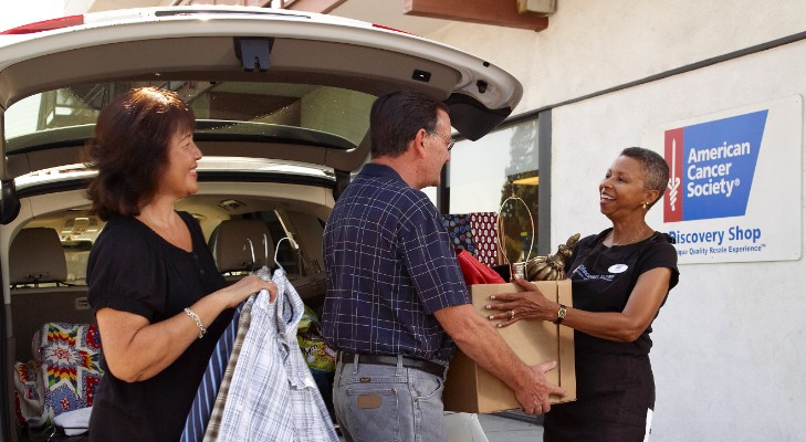 volunteer helping customers load their trunk with products