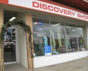 "Close-up of the front of the Discovery Shop building with a sign that says ""Discovery Shop""."