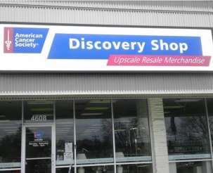 "Close-up of the front of the Discovery Shop building with a sign that says ""American Cancer Society Discovery Shop, Upscale Resale Merchandise"" on the metal roof."