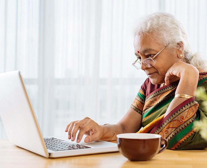 Serious elderly Indian woman working on laptop