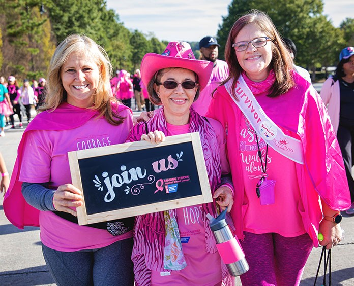 three women wearing pink holding a join us sign for volunteer opportunities