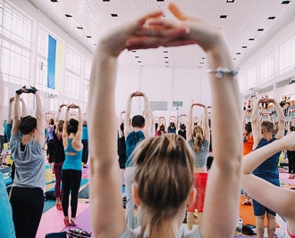 large room full of people stretching above their head in a yoga class
