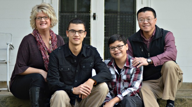 Jill Chang, her husband and two sons sitting on porch steps