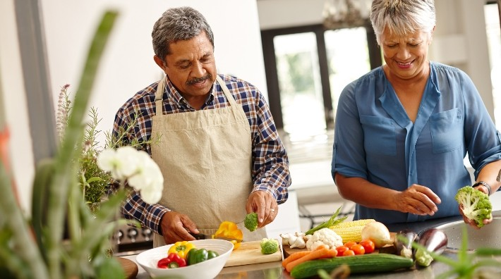 Man and woman chopping vegetables
