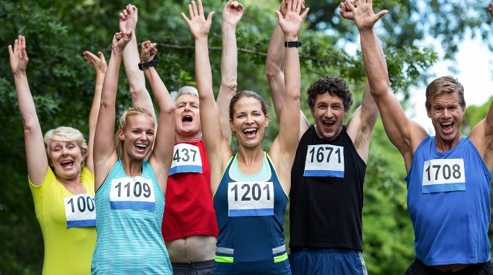 a group of male and female runners celebrate after completing a race
