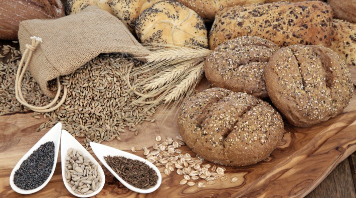 a selection of whole wheat breads and seeds laying on table