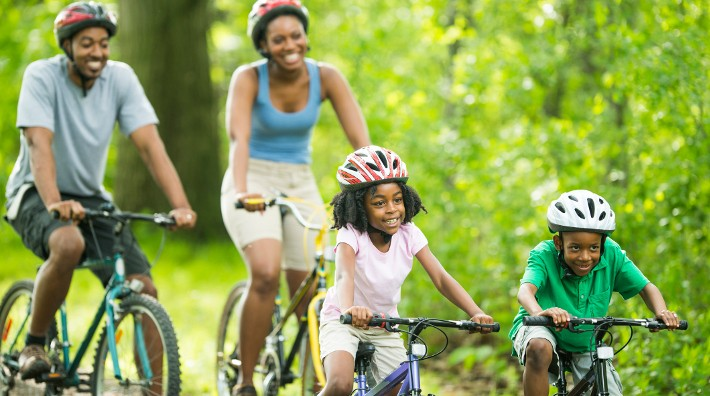 African American family cycling on a forest trail.