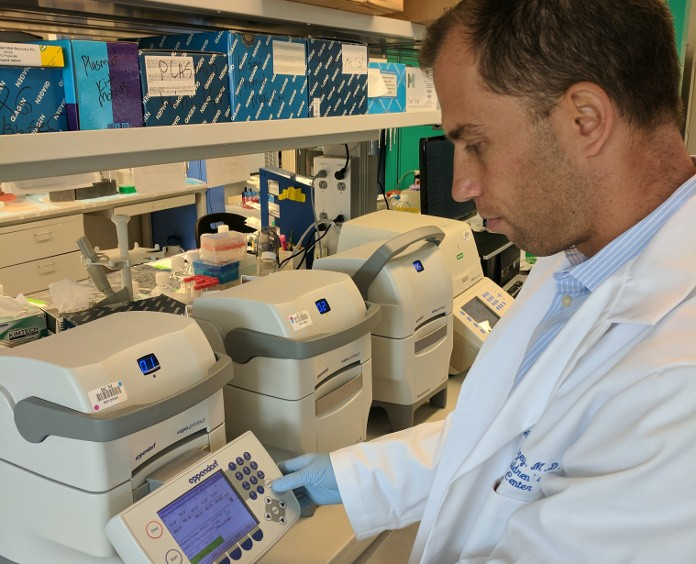 "Dr. Andras Heczey checks the settings of his ""molecular copier,"" a PCR machine, which copies, or amplifies, DNA segments."