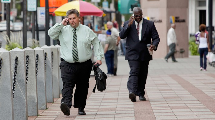 two overweight men talk on their cell phones while walking down a city street