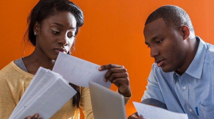 worried couple sort through paperwork at desk