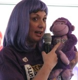 photo of Cynthia Dickson speaking at a Relay for Life event in a purple wig and holding a stuffed monkey named Edsl