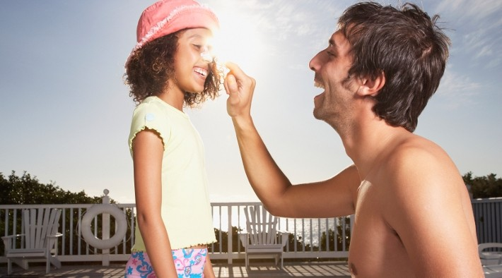 father applies sunscreen to daughter by pool