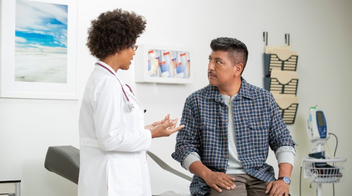 female doctor advising a middle aged male patient in exam room