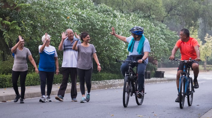 A group of active seniors in the park greet each other as they pass on their morning walk and bike ride