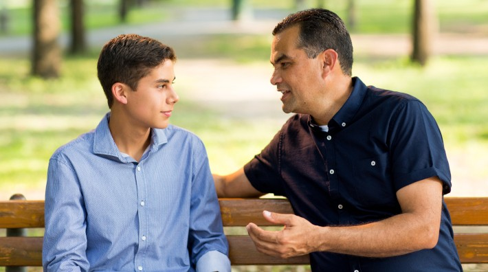 Father and his teenage son sitting on a bench, talking and looking at each other