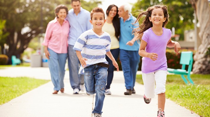 young brother and sister run on a sidewalk with their mom, dad, grandmother and grandfather in the background