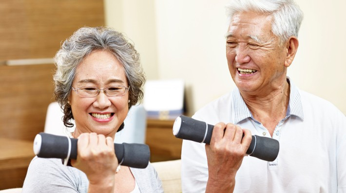 happy senior couple exercising with hand weights