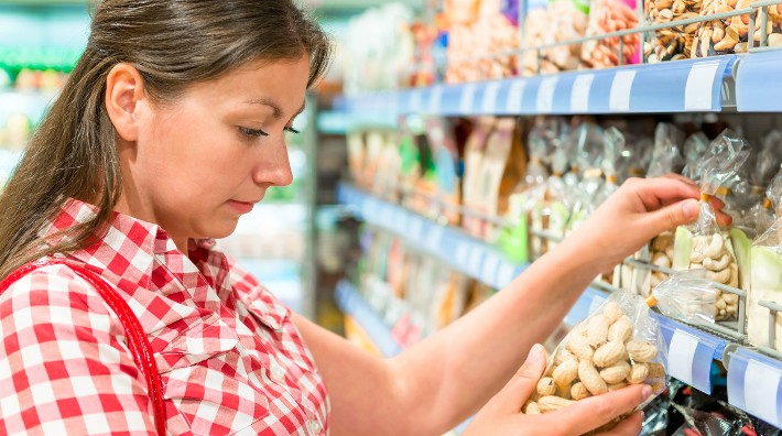 woman chooses a bag of peanuts in a grocery store aisle