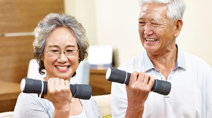 happy senior Asian couple lift hand weights