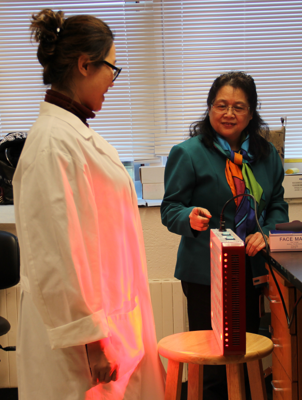 Dr. Mei Wu's research fellow stands in front of the low-level laser they're testing as light therapy to ease intestinal side effects during certain types of chemotherapy.