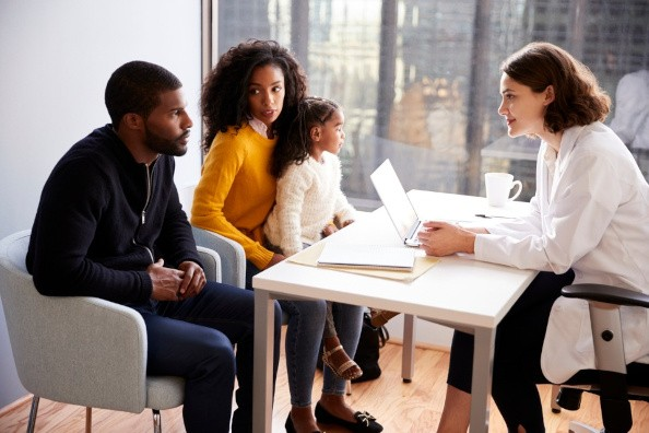 Black Parents with Daughter Across Desk from Doctor