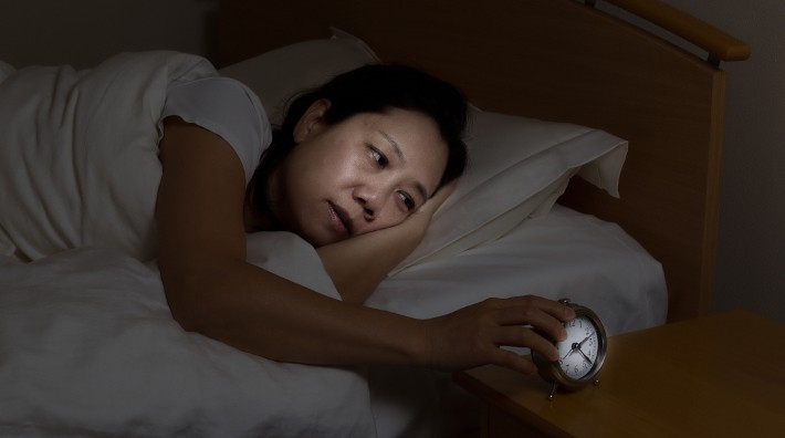 sleep deprived woman lies awake in bed and checks her alarm clock
