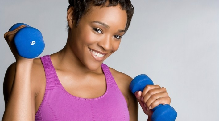 smiling woman holds hand weights