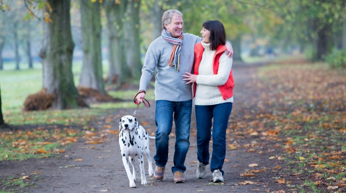 A mature couple walk through a woodland area smiling and laughing while they walk their dalmatian dog