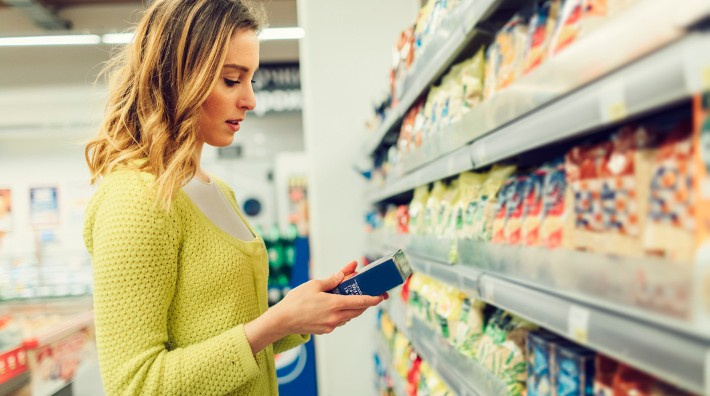 woman reads food label on box in grocery store aisle