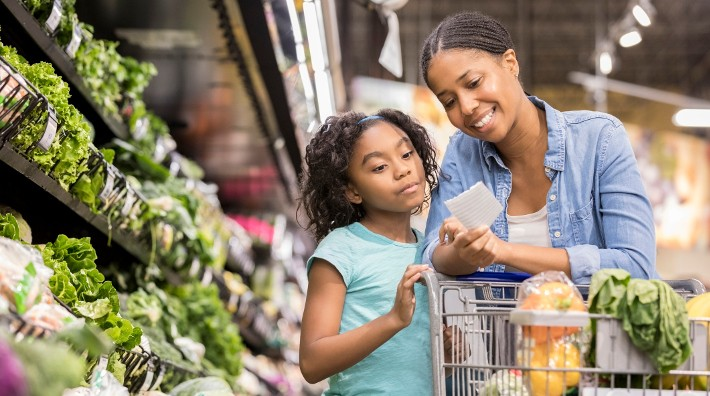 a mom and young daughter go over their shopping list in a grocery store produce aisle