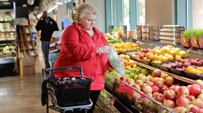 overweight woman buying apples