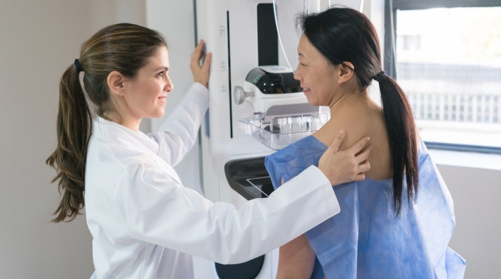 tech or nurse helping a patient get in position for a mammogram