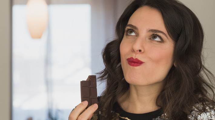 close up of woman's face as she enjoys a bar of chocolate