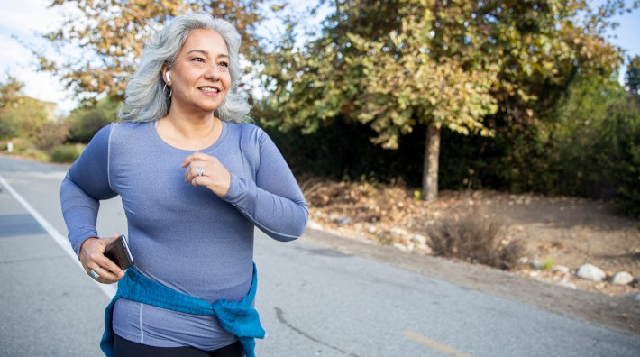 senior woman jogging outside with earphones